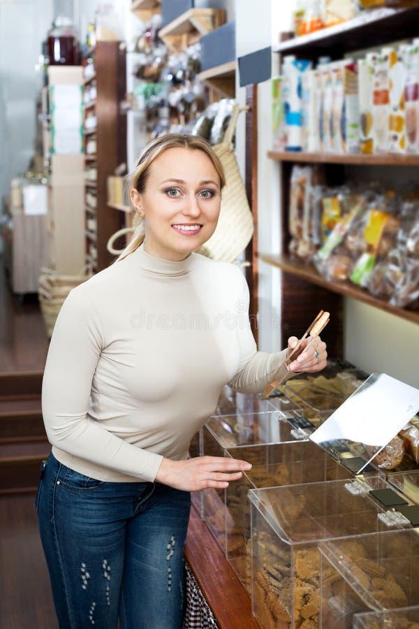 Женщина стоя рядом с контейнерами с высушенными печеньями стоковые изображения