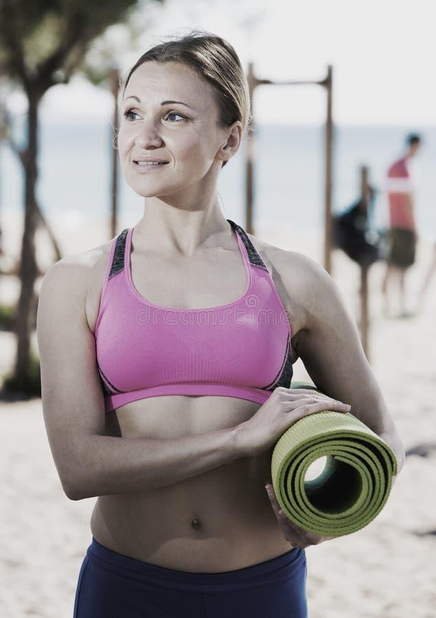 Женщина стоя с гимнастической циновкой стоковое фото rf