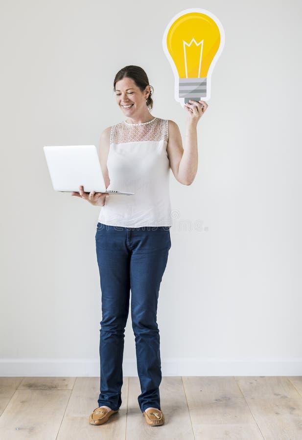 Женщина стоя с компьтер-книжкой и электрической лампочкой стоковые фотографии rf