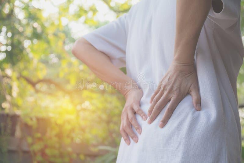 Женщина страдая от backache, повреждение позвоночника и мышца выдают стоковые фото