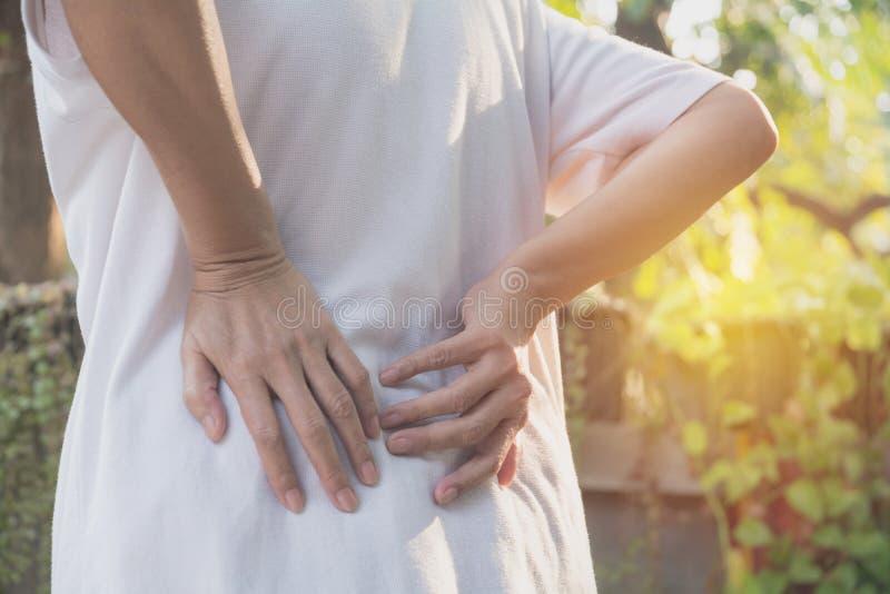 Женщина страдая от backache, повреждение позвоночника и мышца выдают стоковое изображение rf