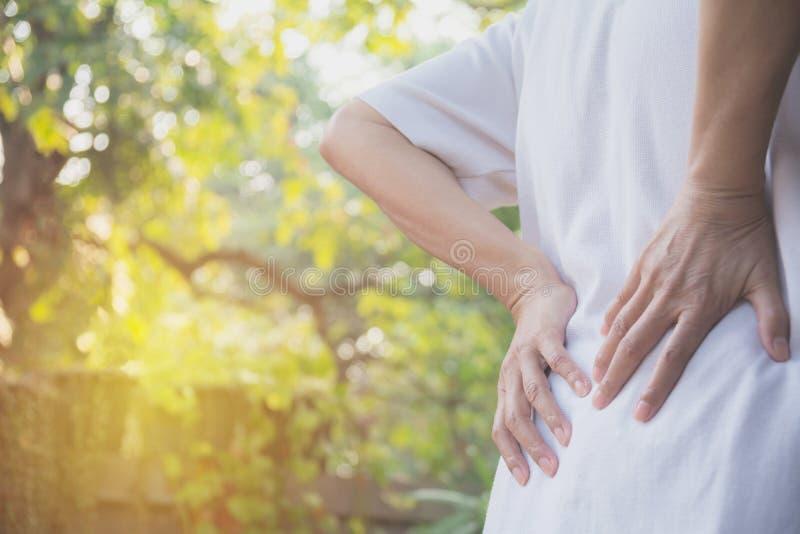 Женщина страдая от backache, повреждение позвоночника и мышца выдают стоковые изображения rf