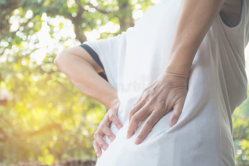 Женщина страдая от backache, повреждение позвоночника и мышца выдают стоковое фото
