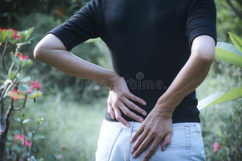 Женщина страдая от backache, повреждение позвоночника и мышца выдают стоковое изображение