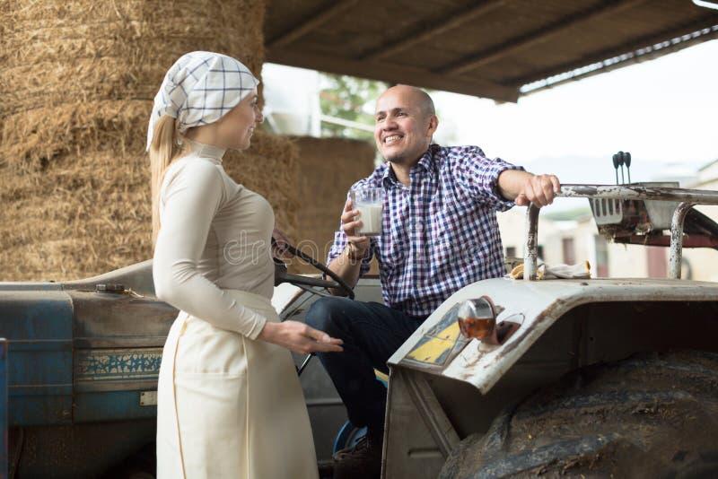 Женщина страны дать для того чтобы укомплектовать личным составом стекло водителя трактора молока на ферме стоковая фотография