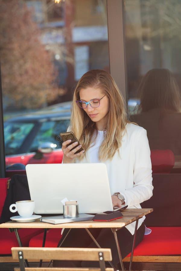 Женщина студента сидит в кафе с беседой компьтер-книжки на умном телефоне, outd стоковое изображение
