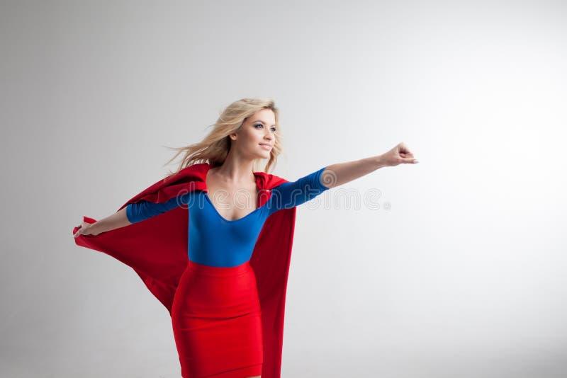 Женщина супергероя Молодая и красивая блондинка в изображении superheroine в красный расти накидки стоковые изображения