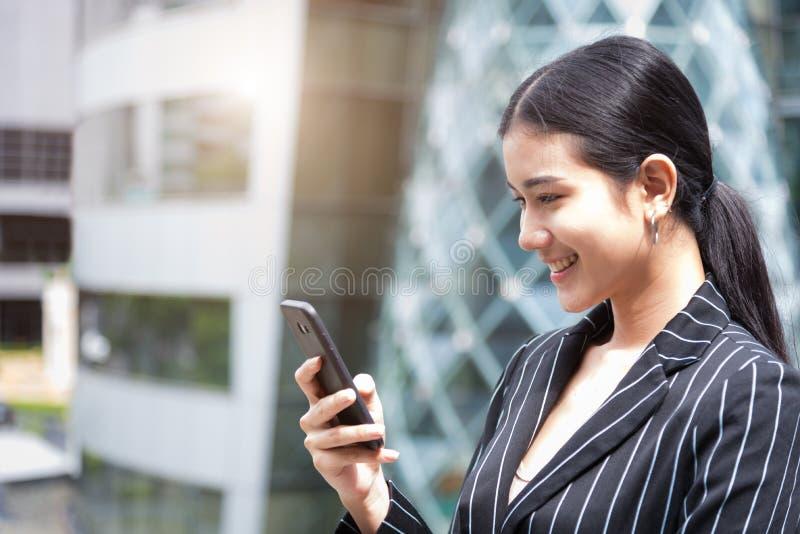 Женщина счастливой красоты азиатская смотря умный телефон пока усмехающся в городской предпосылке Технология и концепция образа ж стоковые изображения rf