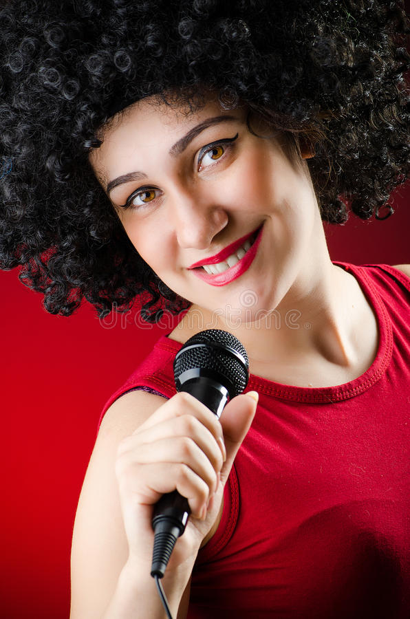 Женщина с афро стилем причёсок поя в караоке стоковые изображения
