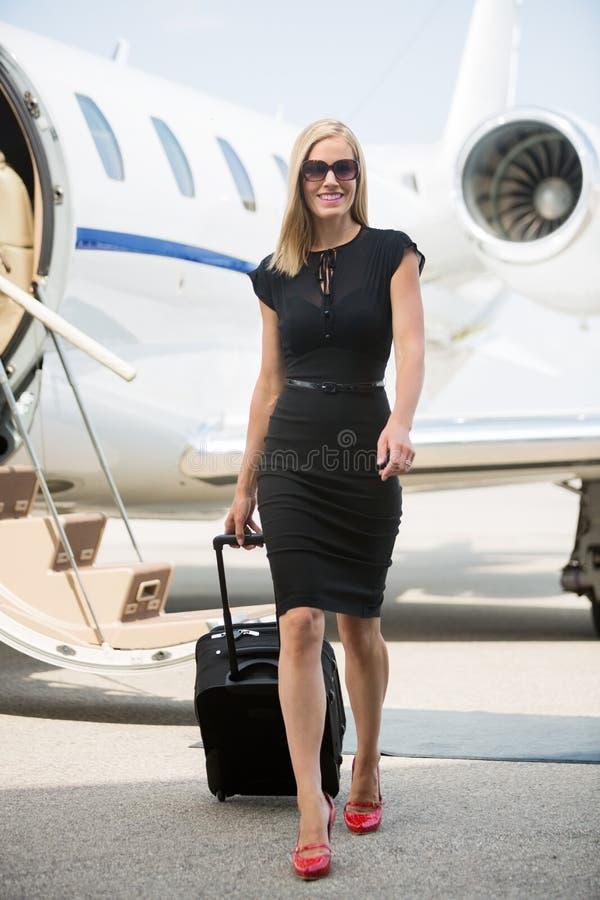 Женщина с багажом идя против частного самолета стоковые изображения rf