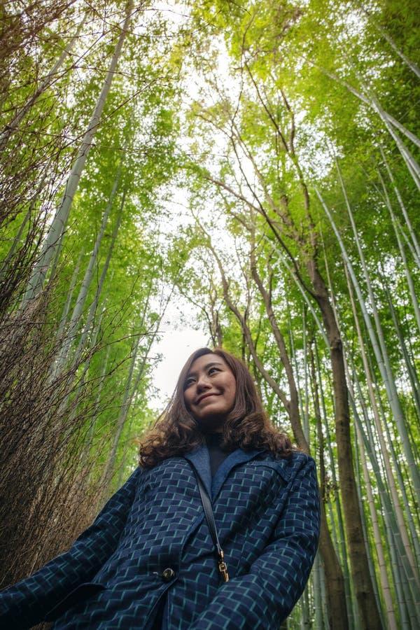 Женщина с бамбуковым лесом в предпосылке стоковое изображение