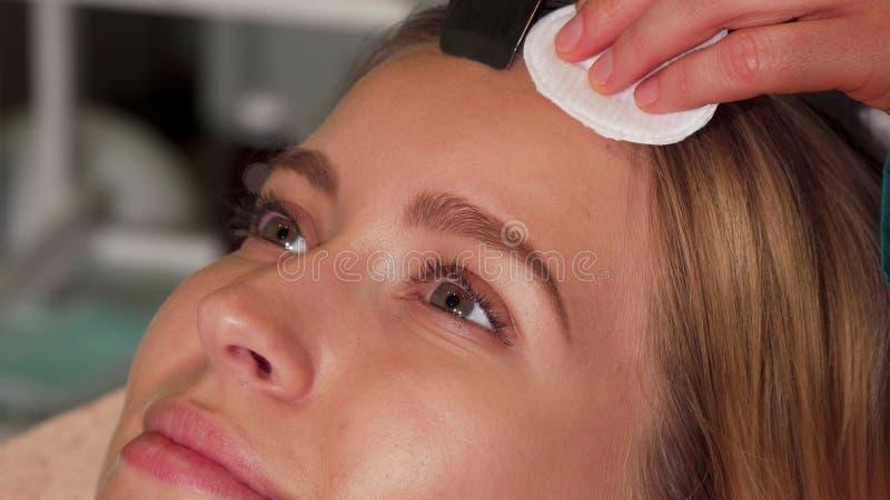 Женщина с безупречной кожей наслаждаясь ультразвуковым уходом за лицом стоковая фотография