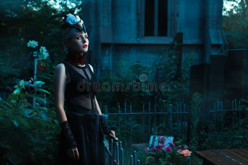 Женщина с белизной наблюдает положение в кладбище на ноче стоковое фото rf
