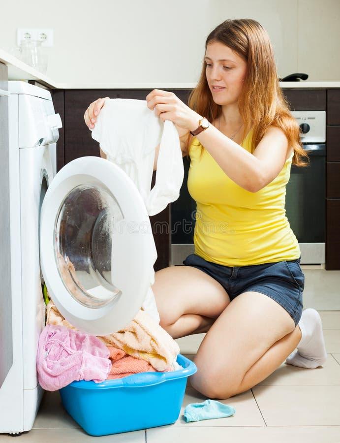 Женщина с белизной одевает около стиральной машины стоковая фотография