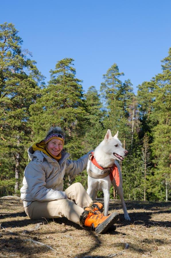 Женщина с белой собакой в древесине стоковое фото