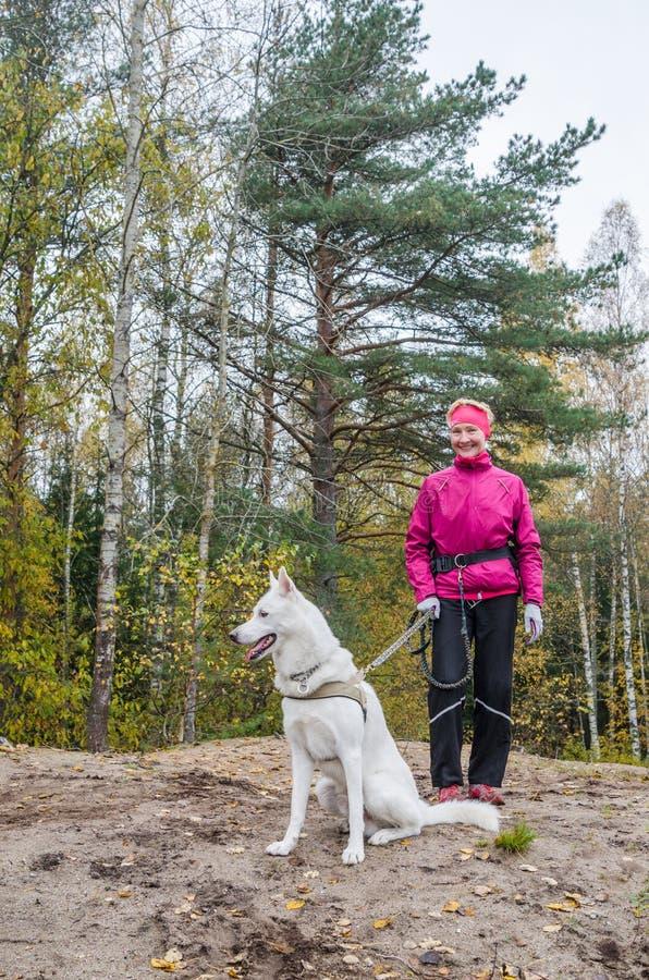 Женщина с белой собакой в древесине стоковая фотография rf