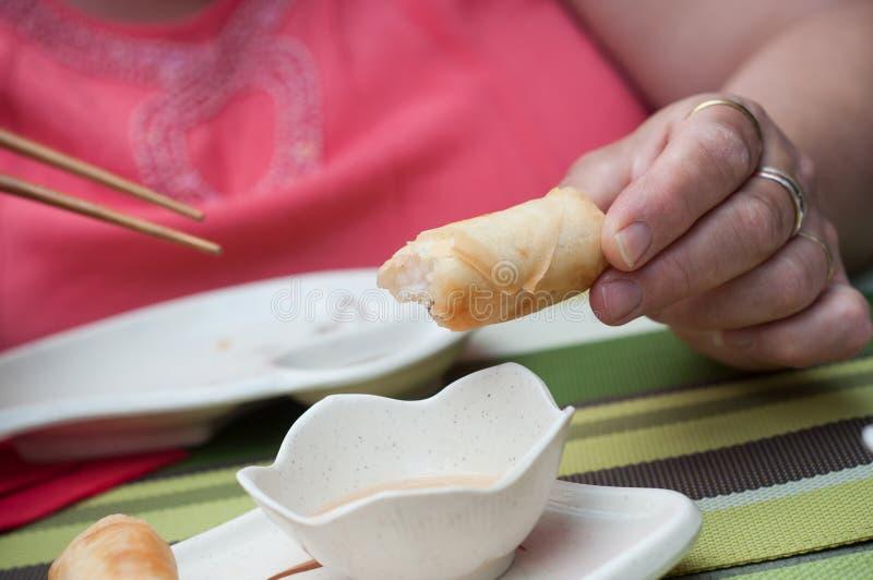 Женщина с блинчиками с начинкой на палочках на китайце стоковое изображение