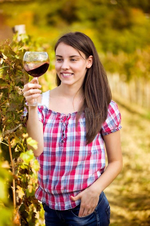 Женщина с бокалом вина в винограднике стоковое фото