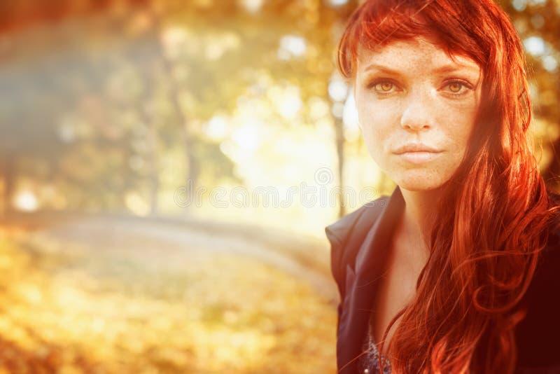 Женщина с веснушками и красные длинные волосы в падении паркуют стоковое фото