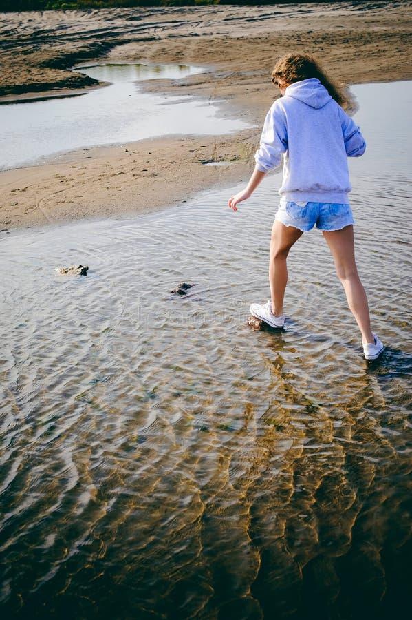 женщина с вьющиеся волосы, романс молодости, прогулка путешествием на день теплого лета солнечный на песчаном пляже с водой стоковое изображение