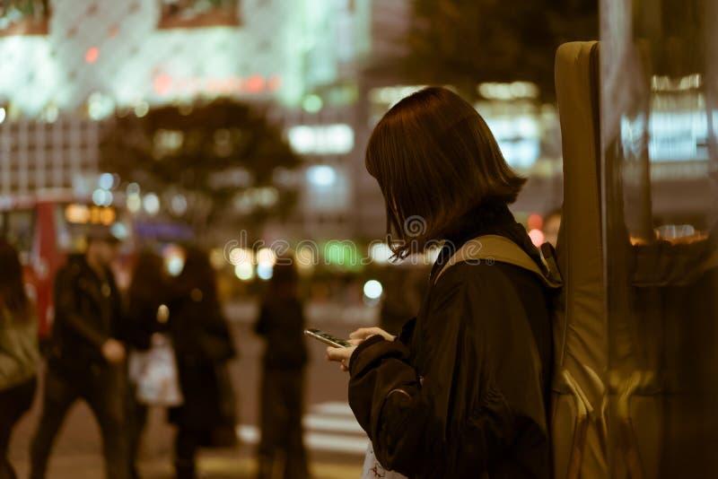 Женщина с гитарой на ей назад отправляя СМС на улице в Shibuya, токио, Японии стоковые изображения rf