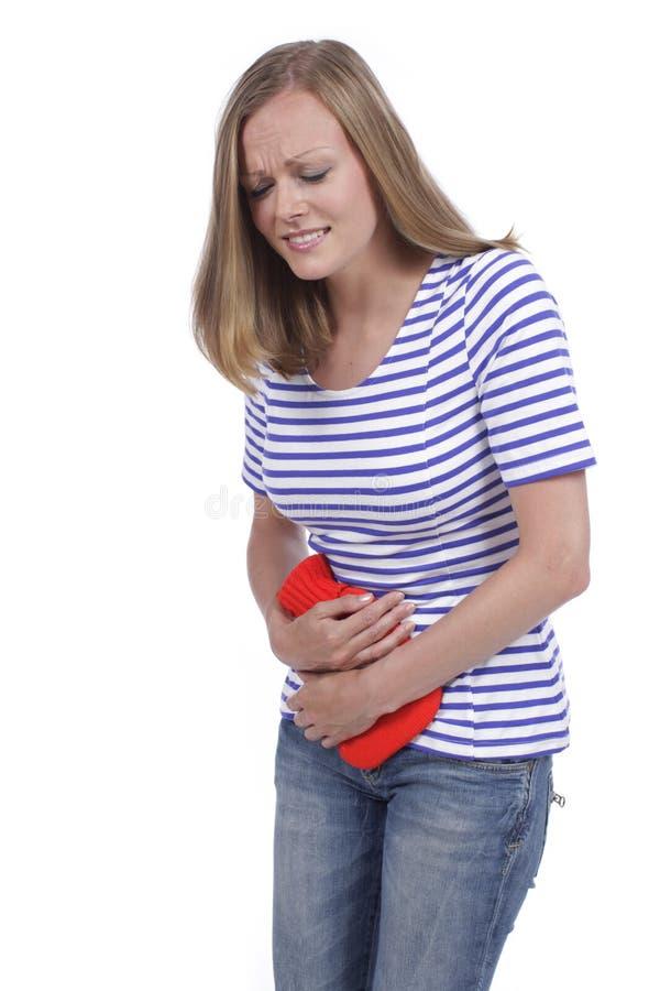Женщина с горячей бутылкой и болью в животе стоковая фотография rf