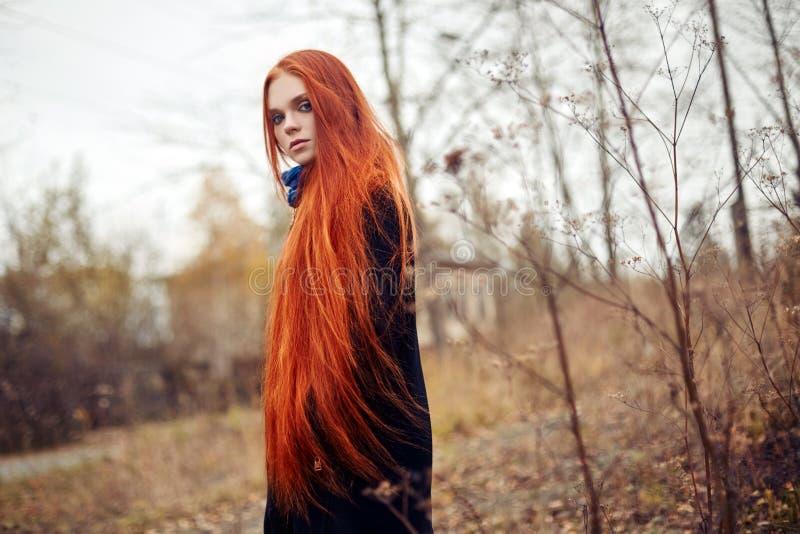 Женщина с длинными красными волосами идет в осень на улице Загадочный мечтательный взгляд и изображение девушки Идти женщины Redh стоковое фото