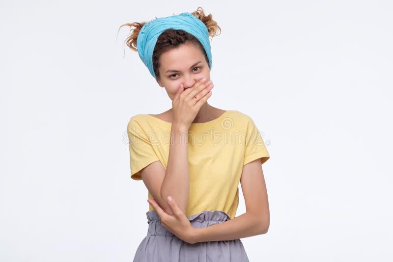 Женщина с дредлоками, разрывающаяся в смех, закрывая рот руками стоковые изображения