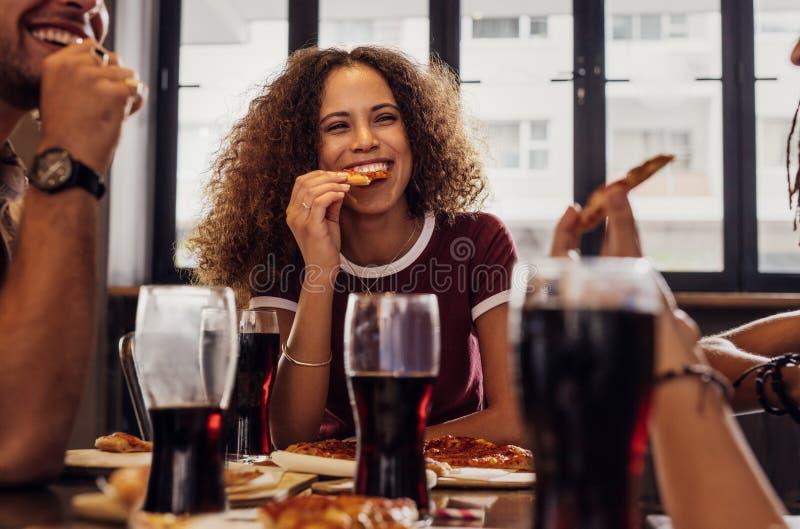 Женщина с друзьями наслаждаясь едой стоковое фото