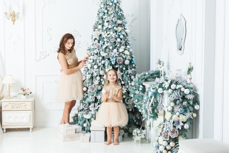 Женщина с ее дочерью украсить рождественскую елку стоковое изображение