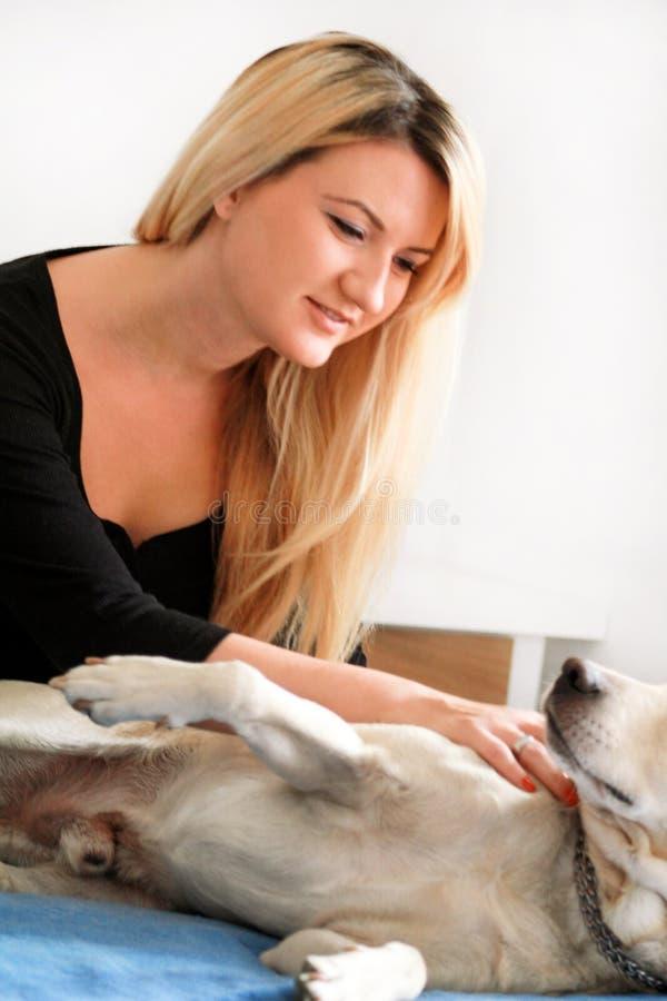 Женщина с ее собакой в кровати дома, ослабляющ в спальне Красивая девушка играет, совместно и petting с собакой в кровати стоковое фото rf
