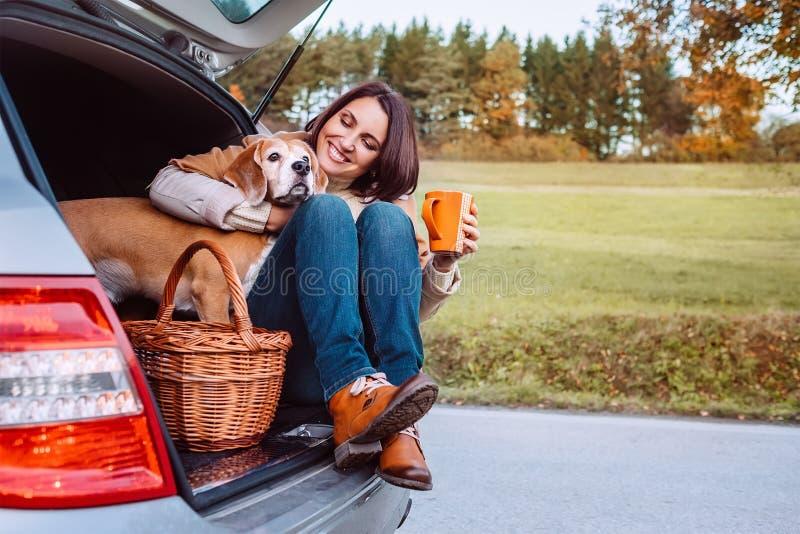 Женщина с ее собакой имеет время чая во время их trav автомобиля осени стоковые изображения rf