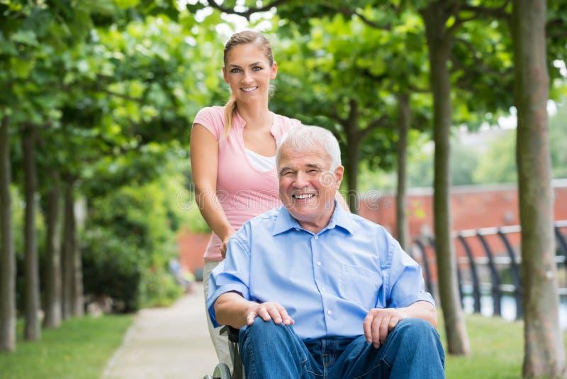 Женщина с ее старым старшим отцом на кресло-коляске стоковое фото rf