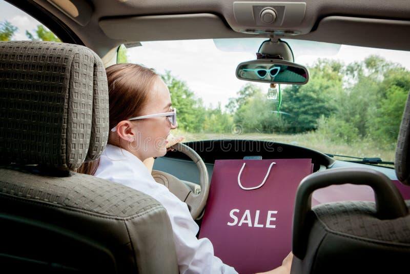 Женщина с ее хозяйственными сумками в автомобильную ходя по магазинам концепцию стоковое изображение