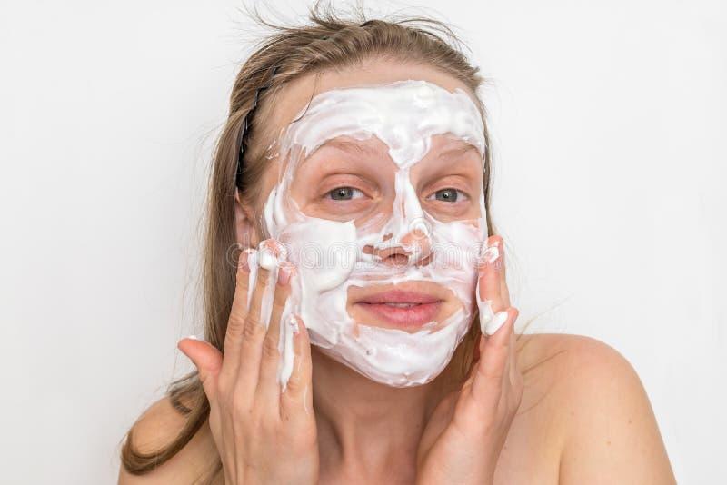 Женщина с естественной белой маской сливк на ее стороне стоковое фото rf