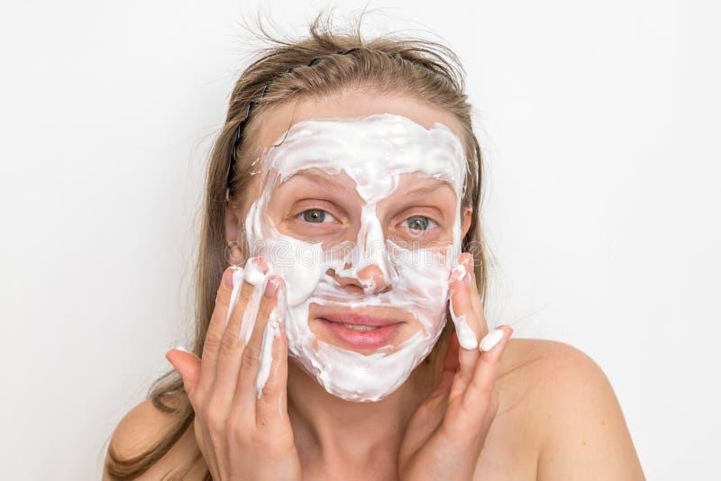 Женщина с естественной белой маской сливк на ее стороне стоковые фотографии rf