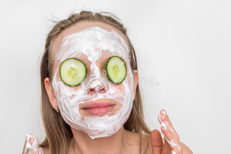 Женщина с естественной маской сливк и огурцы на ее стороне стоковые изображения rf