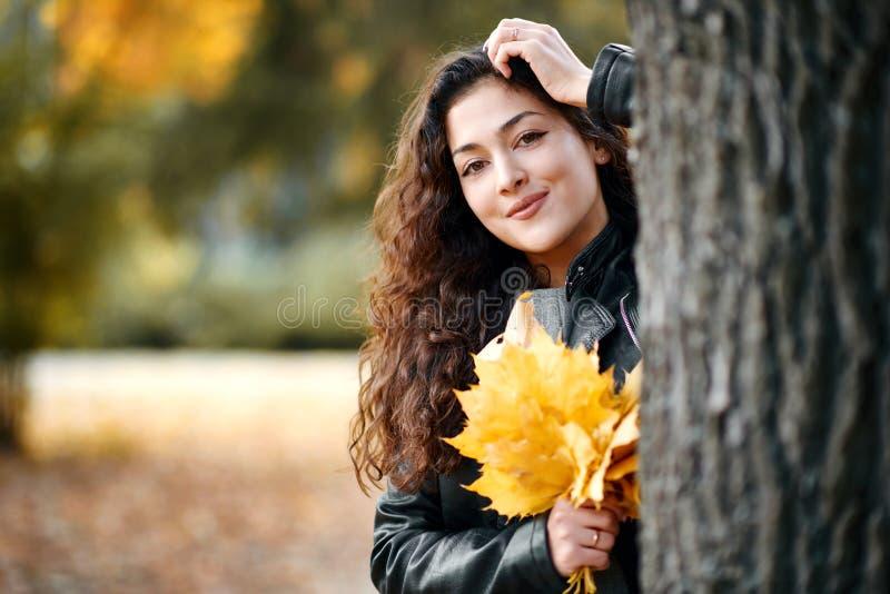 Женщина с желтыми листьями стоит около большого дерева в парке города осени Крупный план портрета стоковое изображение rf