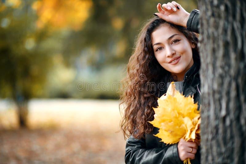 Женщина с желтыми листьями стоит около большого дерева в парке города осени Крупный план портрета стоковые изображения rf