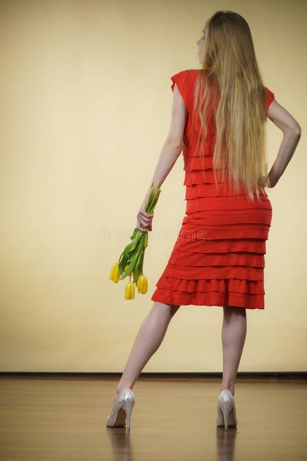 Женщина с желтым пуком тюльпанов, задним взглядом стоковое изображение rf