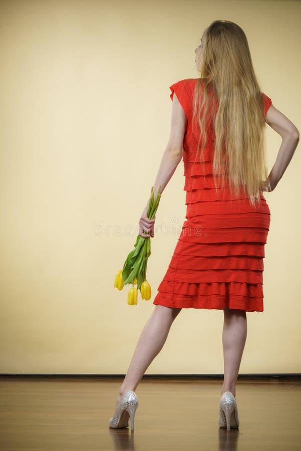 Женщина с желтым пуком тюльпанов, задним взглядом стоковые изображения rf