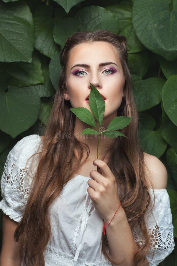 Женщина с зелеными лист стоковые изображения