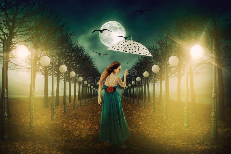 Женщина с зонтиком идя вне в уличные светы стоковая фотография