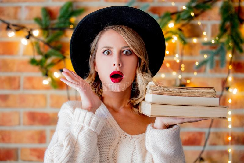 Женщина с книгами и светами рождества стоковая фотография