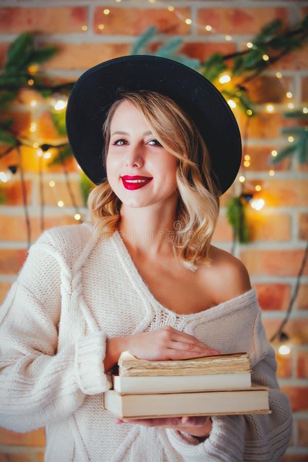 Женщина с книгами и светами рождества стоковые изображения rf