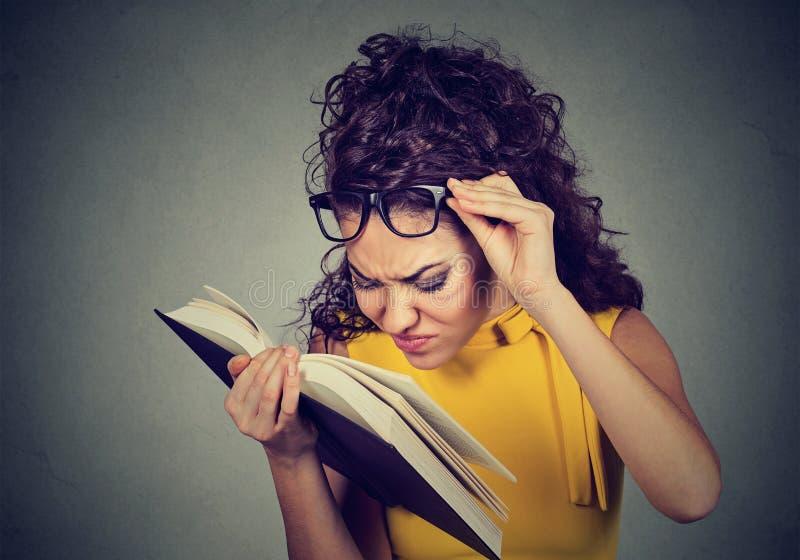 Женщина с книгой чтения стекел имеет проблемы зрения стоковое изображение