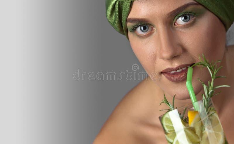 Женщина с коктеилем лимона и известки с ветвью rosemar стоковые изображения
