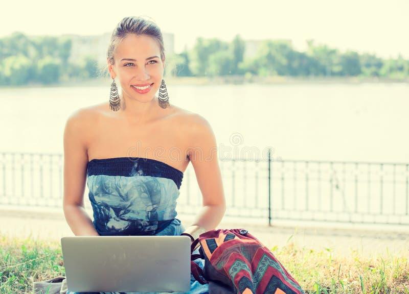 Женщина с компьтер-книжкой внешней в парке стоковые изображения rf