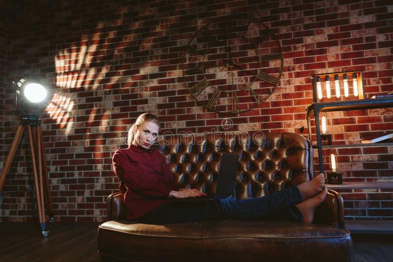 Женщина с компьтер-книжкой в просторной квартире стоковое изображение rf