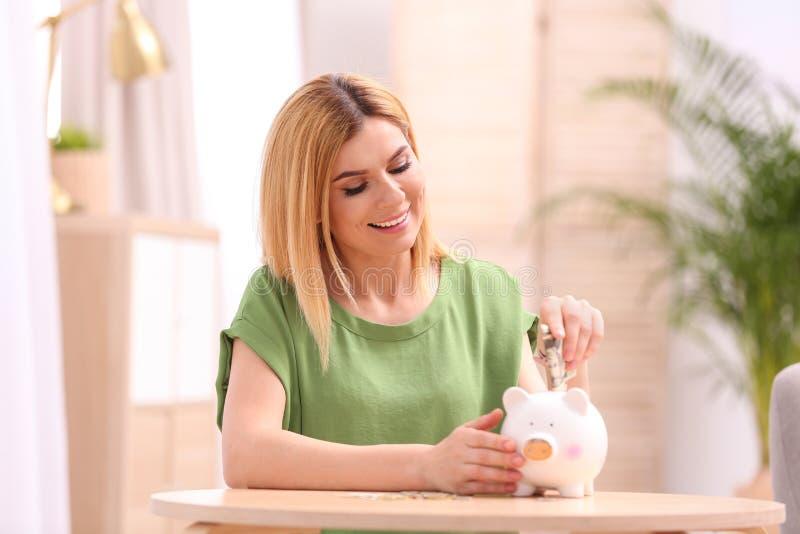 Женщина с копилкой и деньгами стоковая фотография